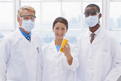 Three doctors standing with female doctor holding prescription medication, portrait